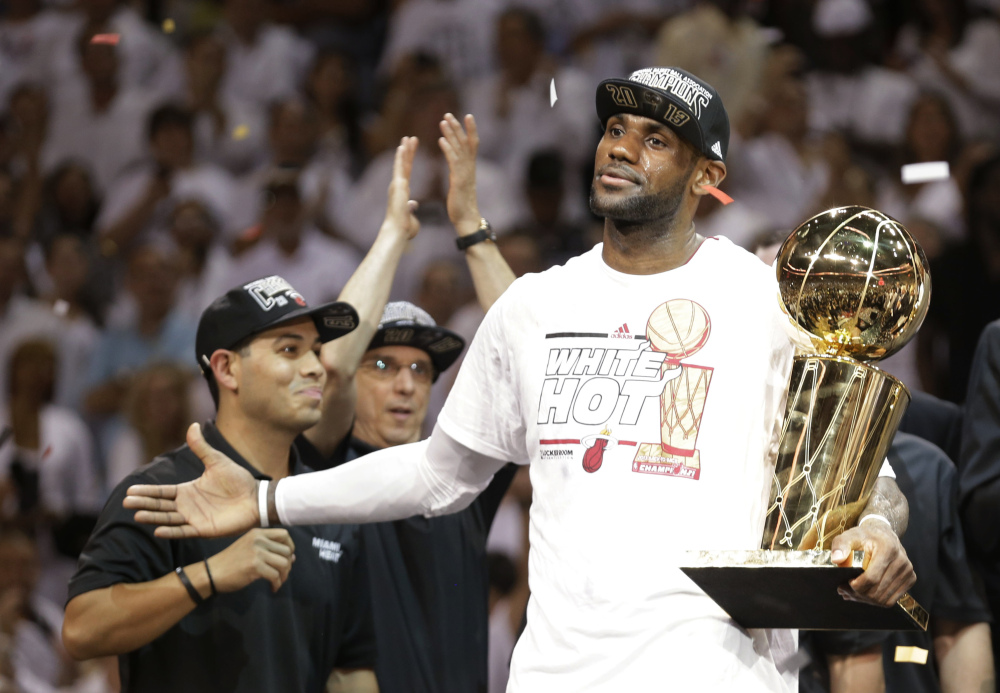 Miami Heat's LeBron James holds the the Larry O'Brien NBA championship trophy last year.