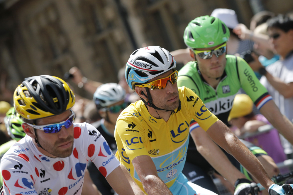 France's Cyril Lemoine, wearing the best climber's dotted jersey, and Italy's Vincenzo Nibalia, wearing the overall leader's yellow jersey, ride in the pack during the ceremonial procession prior to the start of the third stage of the Tour de France cycling race in England on Monday.