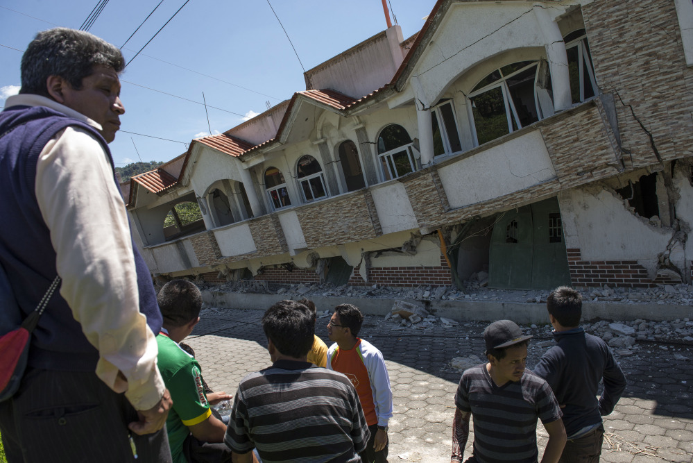 Neighbors gather outside homes that collapsed during an earthquake in San Pedro, Guatemala, on Monday.