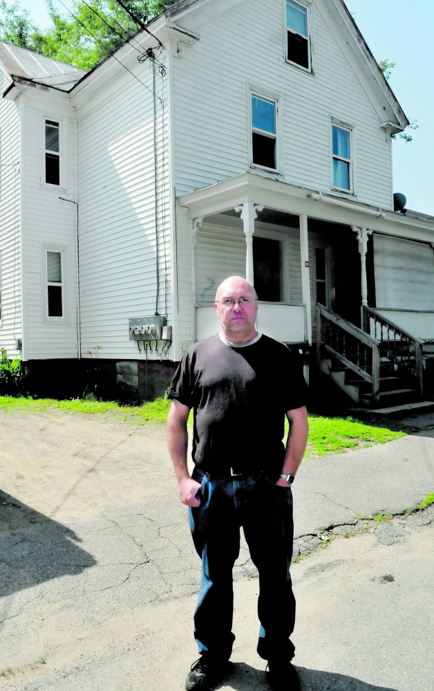 Former Oakland police Officer Jim Hamilton stands outside the Summer Street apartment building in Waterville where he discovered the body of his grandmother Evelyn Pomerleau,in 1989.