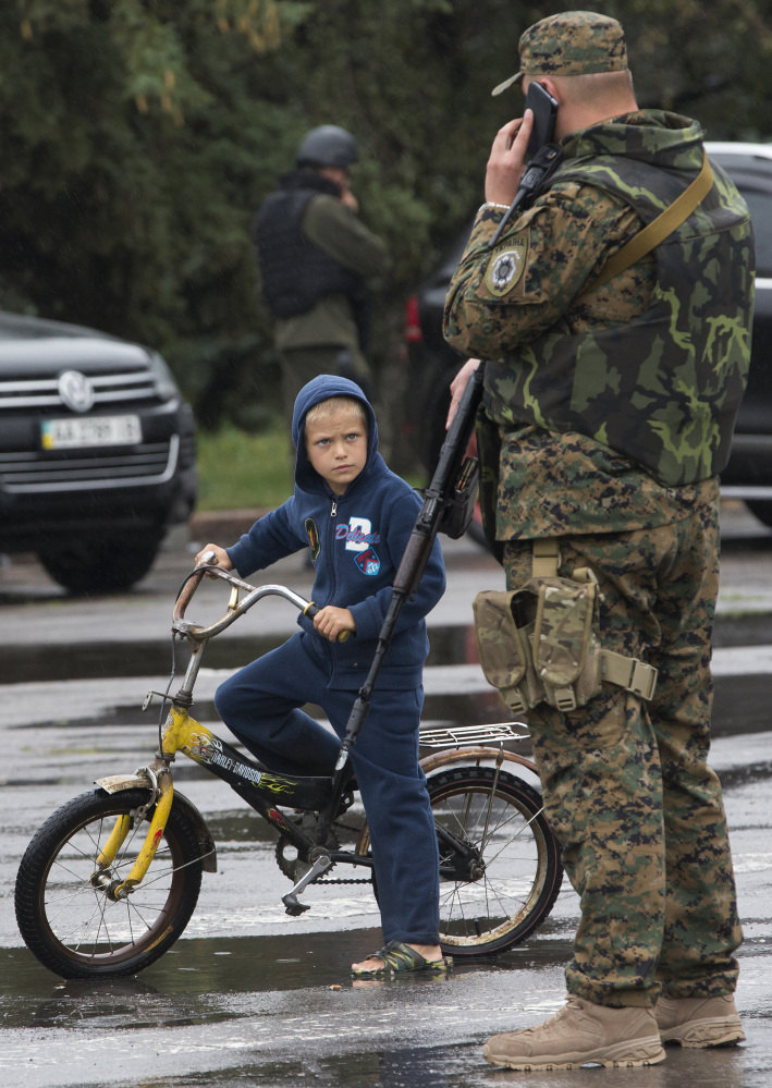 A boy looks at a Ukrainian government army soldier in the city of Slovyansk, in eastern Ukraine, on Monday. After retaking the pro-Russian separatists' stronghold here, the Ukrainian government is turning its attention to Donetsk and Luhansk.