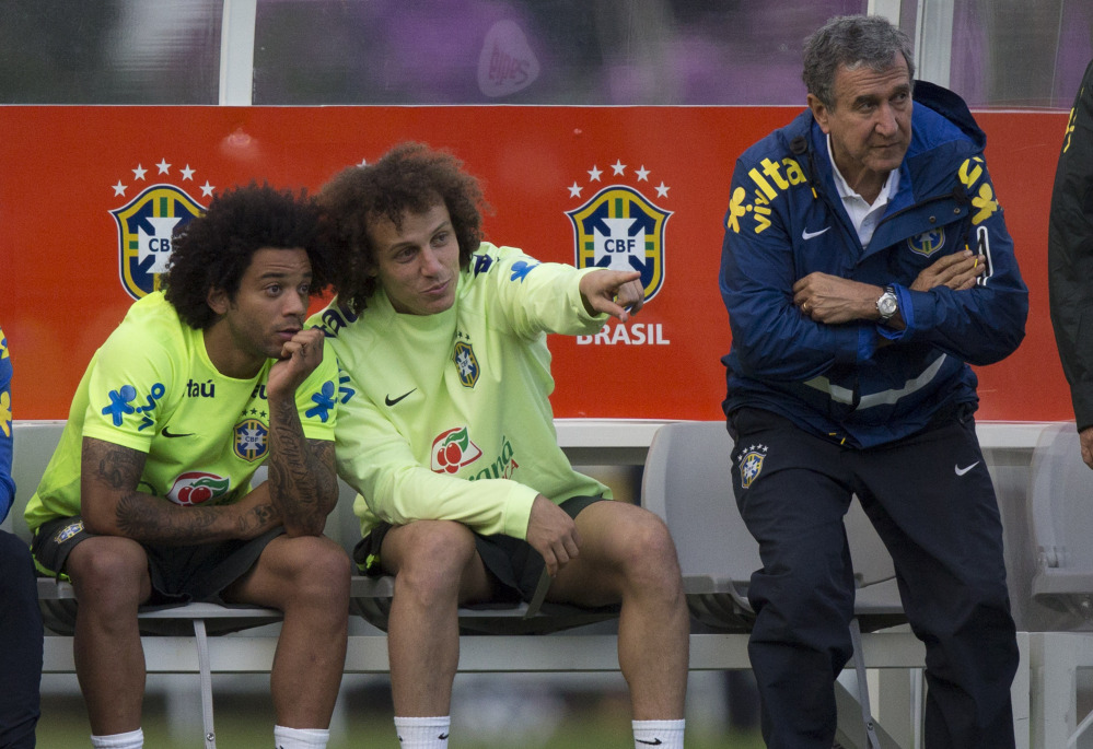 David Luiz, center, talks with Marcelo as Brazil's team coordinator, Carlos Alberto Parreira, stands next to them during practice. Brazil needs players to come through with the loss of Neymar, its star forward.
