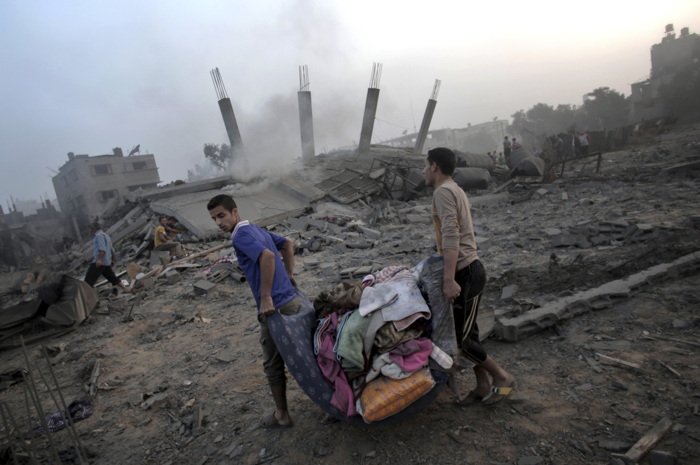 Palestinians try to salvage what they can of their belongings from the rubble of a house destroyed by an overnight Israeli airstrike in Gaza City Tuesday.