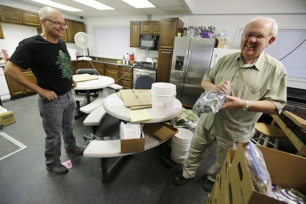 Bob Leeds, owner of Sea of Green Farms, right, has a laugh with farm director Phil Tobias, as they load packets of recreational marijuana into boxes, Tuesday in Seattle, for delivery to a store in Bellingham, Wash.