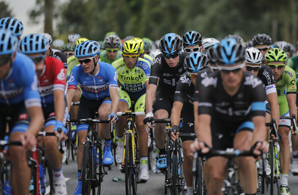 Spain's Alberto Contador, center in fluorescent jersey, and Britain's Christopher Froome, center with bandaged wrist, ride in the pack during the fourth stage of the Tour de France on Tuesday.