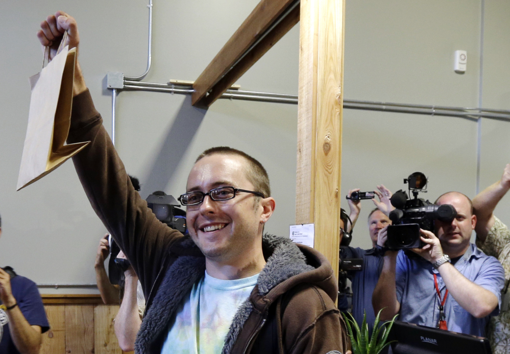 Cale Holdsworth, of Abeline, Kan., holds up his purchase after being the first in line to buy legal recreational marijuana at Top Shelf Cannabis, Tuesday in Bellingham, Wash. Holdsworth had been in line since 4:00 a.m.