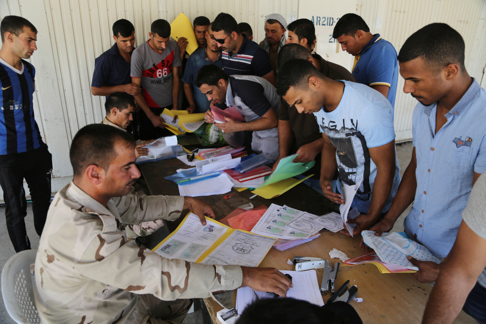 Iraqi men check in at the main army recruiting center as they volunteer for military services in Baghdad, Iraq, Wednesday.