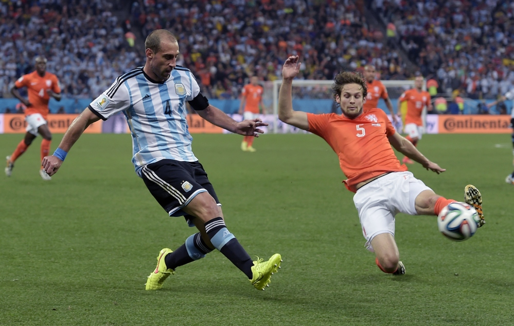 Netherlands' Daley Blind, right, slides in to block a cross from Argentina's Pablo Zabaleta during the World Cup semifinal soccer match between the Netherlands and Argentina at the Itaquerao Stadium in Sao Paulo Brazil, on Wednesday.
