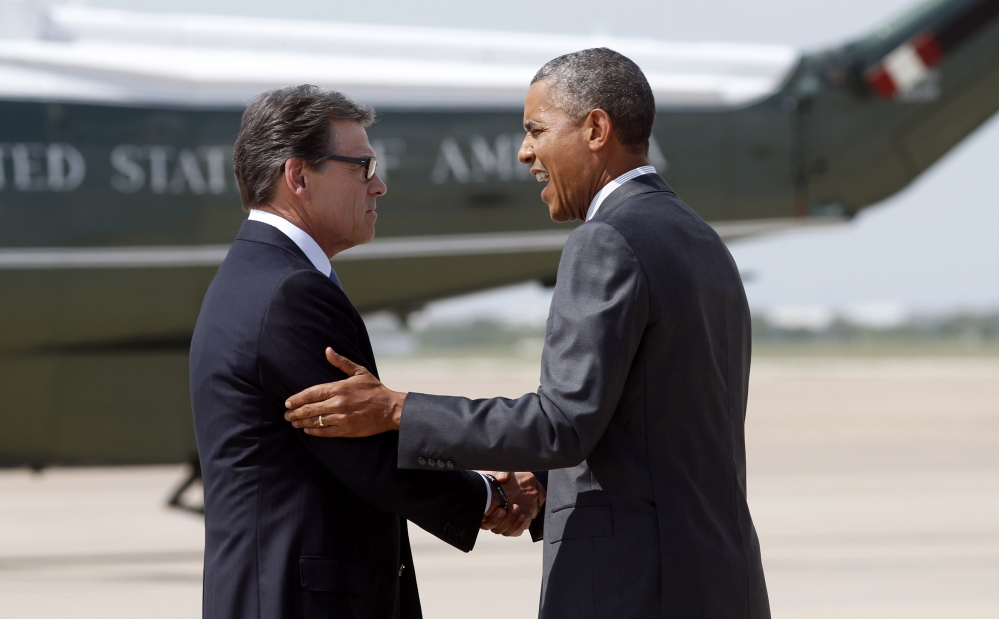 Texas Gov. Rick Perry greets President Obama upon his arrival in Dallas to discuss a surge of young people crossing the U.S.-Mexico border.