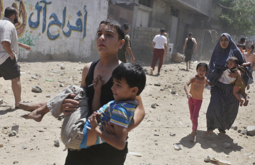 Palestinians flee following what police said was an Israeli airstrike on a house in Gaza City on Wednesday. At least 23 people were killed across Gaza by a bombardment Israel said may be just the start of a lengthy offensive.