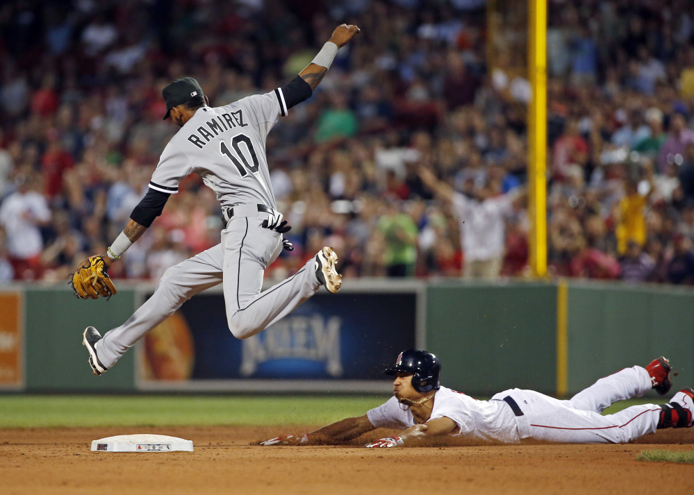 Boston's Mookie Betts slides into second base with a double as Chicago shortstop Alexei Ramirez leaps for the ball during the Red Sox' eighth-inning rally Wednesday night.