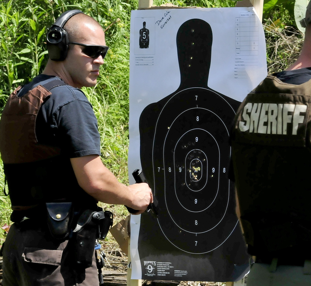 "Somerset County Sheriff's Department Deputy David Cole checks his paper target after firing during the Shawn Donahue Memorial ""Shooting Star"" competition in Winslow."