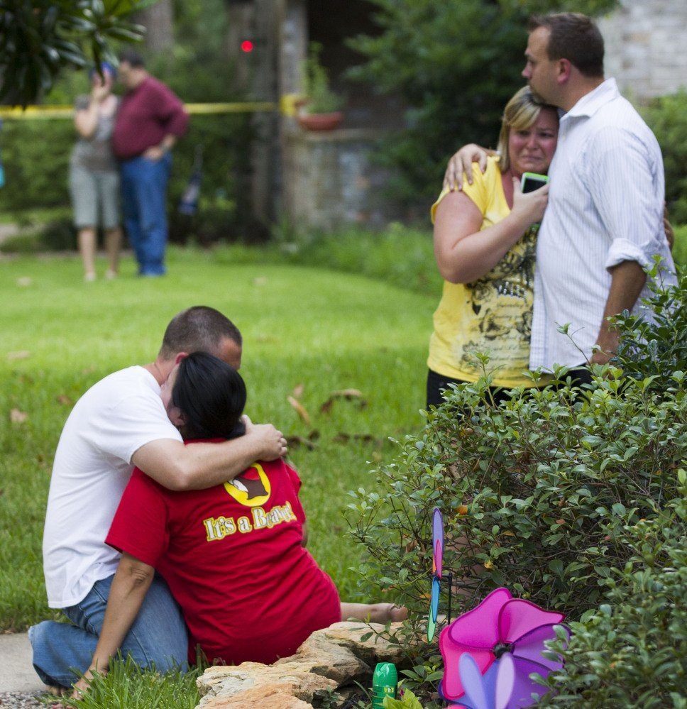 Neighbors embrace each other following a shooting Wednesday in Spring, Texas, a Houston suburb.