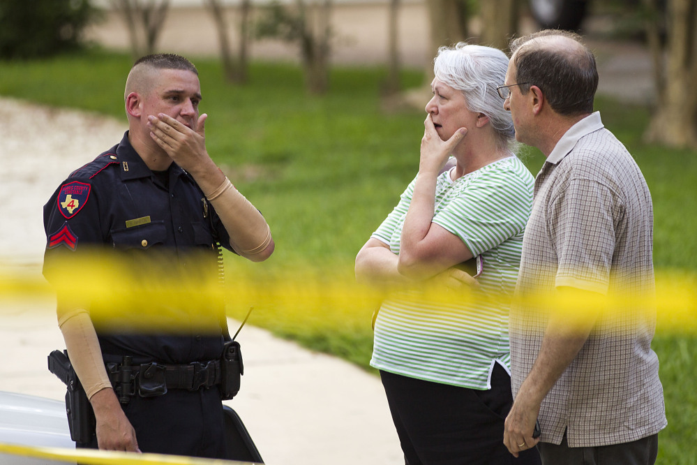 People stand with a law enforcement officer near the scene of a shooting Wednesday in Spring, Texas. A Harris County Sheriff's Office statement says precinct deputy constables were called to the house about 6 p.m. Wednesday and found two adults and three children dead. Another child later died at a hospital.