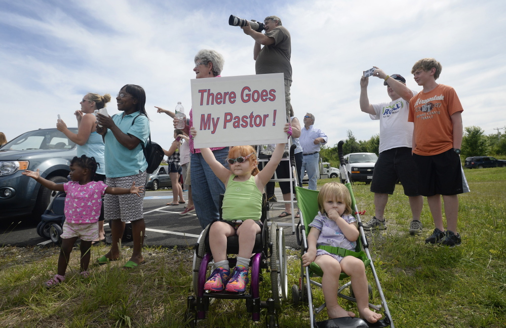 "Four-year-old Sophia Emerson of Biddeford, accompanied by her 1-year-old sister, Natalie, cheers along with other congregants from The Rock Church in Scarborough as their pastor, Lt. Col. Eric Samuelson, made a final flight in an F-15, buzzing the Portland jetport Thursday. Two other F-15 pilots, top left, accompanied him on his ""last mission."""