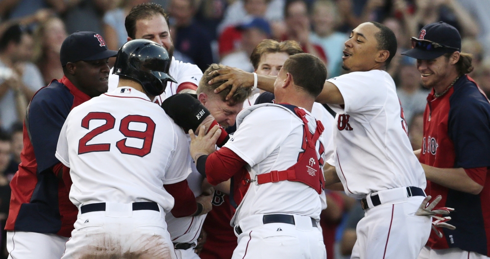 Red Sox pinch hitter Mike Carp, center, is mobbed by teammates after his walk-off RBI single, breaking a 3-3 tie against the Chicago White Sox in the 10th inning of Thursday's game at Fenway Park.
