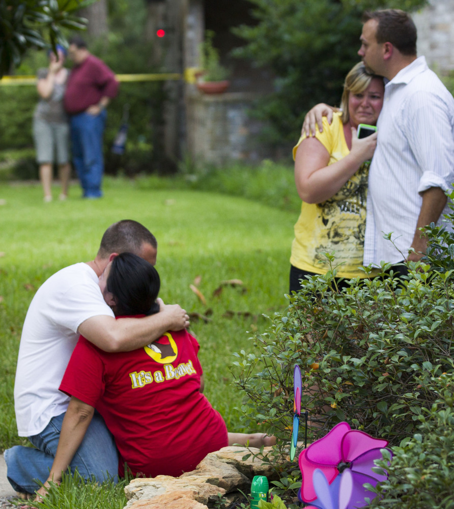 Neighbors embrace each other in suburban Houston after a shooting Wednesday, allegedly by an estranged brother-in-law, killed two parents and four of their five children.