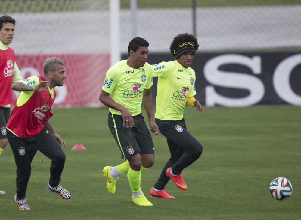 Now comes the game that nobody really wants to play – for third place – but Brazil was back in training Thursday, preparing to meet the Netherlands on Saturday. Willian, right, Paulinho, center, and Daniel Alves fight for the ball at Teresopolis, Brazil.