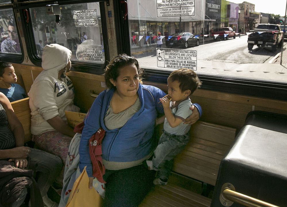 Marta Beltran, 19, of El Salvador holds her young son, Lenny, as they ride a city shuttle bus to the Sacred Heart Catholic Church Shelter in McAllen, Texas.