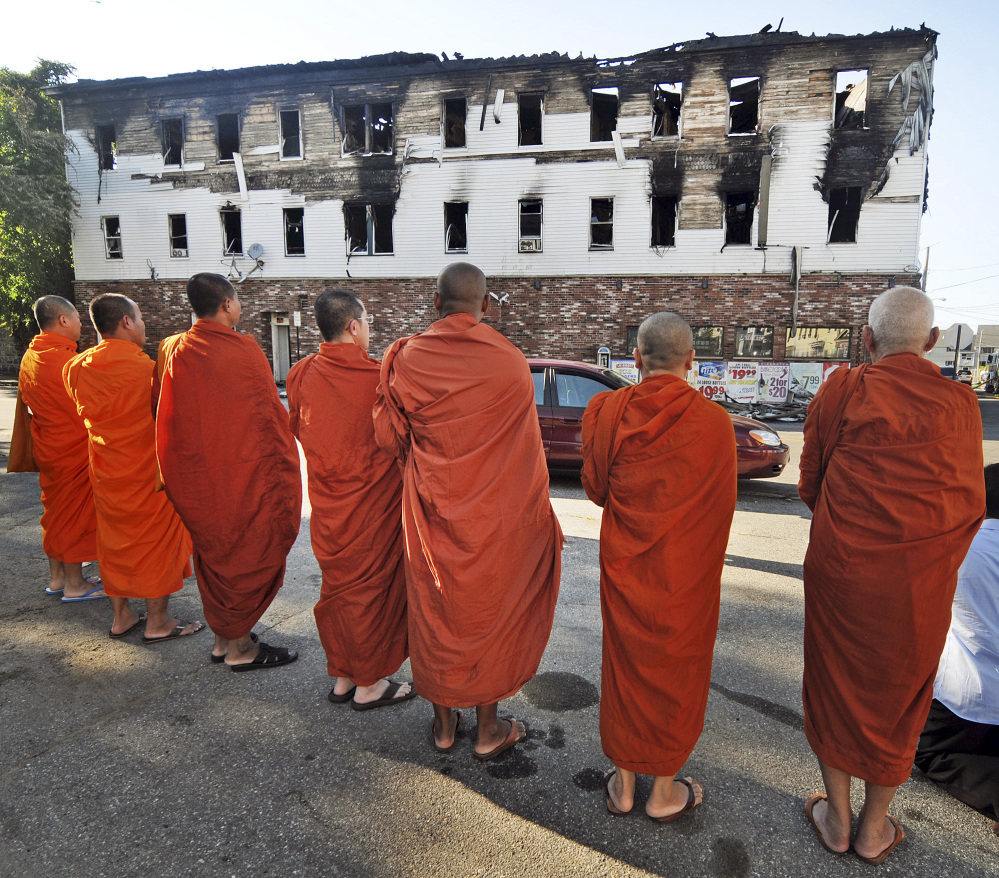 Buddhist monks pray Thursday outside a burned-out apartment building in Lowell, Mass., where seven people, including five members of a family of Cambodian descent, died in a predawn fire. Lowell is home to one of the country's largest Cambodian communities.