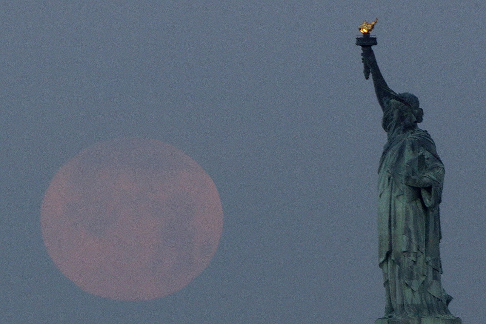 "A ""supermoon"" sets near the Statue of Liberty on June 23, 2013. A larger-than-normal moon called a supermoon happens Saturday."