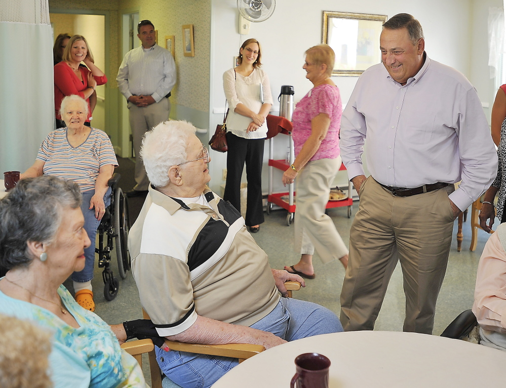 Gov. Paul LePage chats with Ethel and Dominic Oddi at the Coastal Manor nursing home in Yarmouth on Friday. They and others like them will be a key voting bloc for whomever is elected to the Blaine House in November.