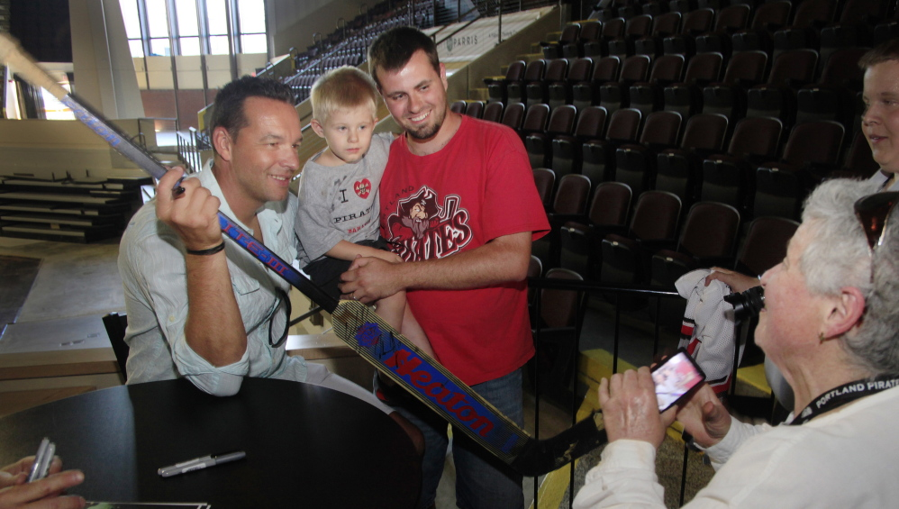Cynthia Reed of Portland takes a photo of former Portland Pirates goalie Olaf Kolzig, left, with fan Scott Prue and Prue's son, Westin, 3, of Biddeford during a reunion Friday of the 1993-94 Pirates team that won the franchise's only Calder Cup championship.