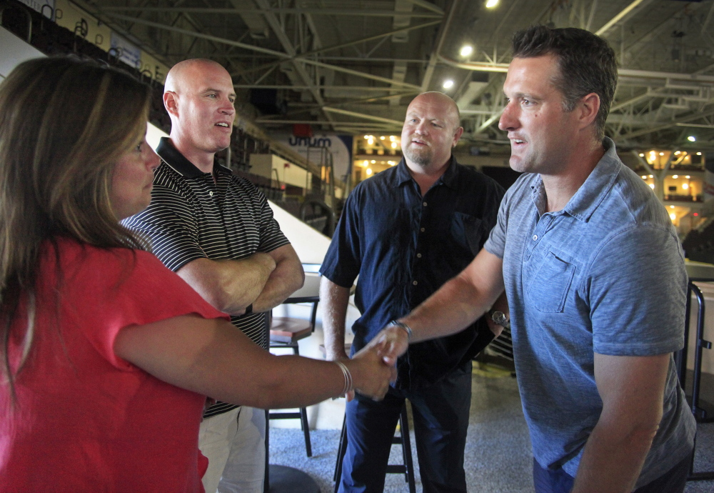 Mary Mathieson of Gorham greets former Portland Pirates defenseman Ken Klee, far right, while her husband, defenseman Jim Mathieson, second from left, looks on with another former teammate, Kerry Clark. Twelve members of the 1993-94 Calder Cup champions gathered Friday for a reunion at Cross Insurance Arena.