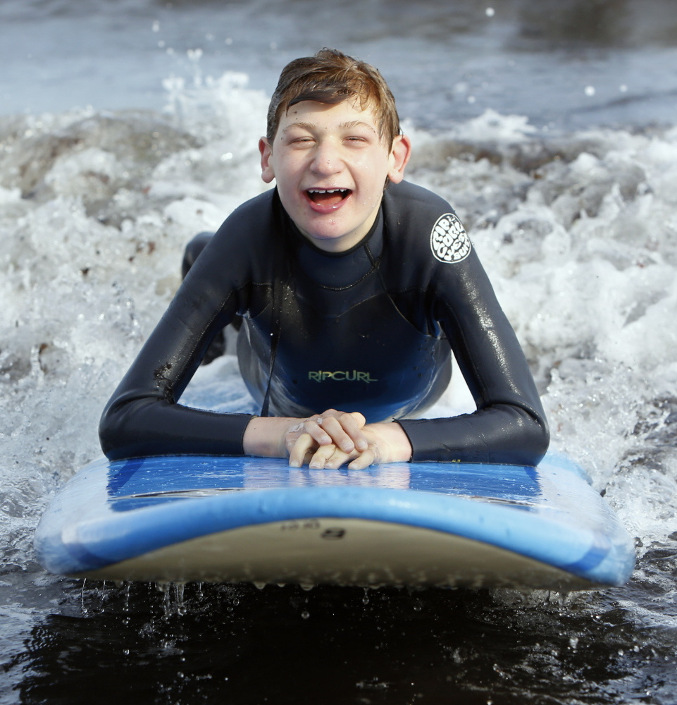 Scotty Wentzell, 13, of North Yarmouth, rides a wave while laying down on a surfboard. Gregory Rec/Staff Photographer