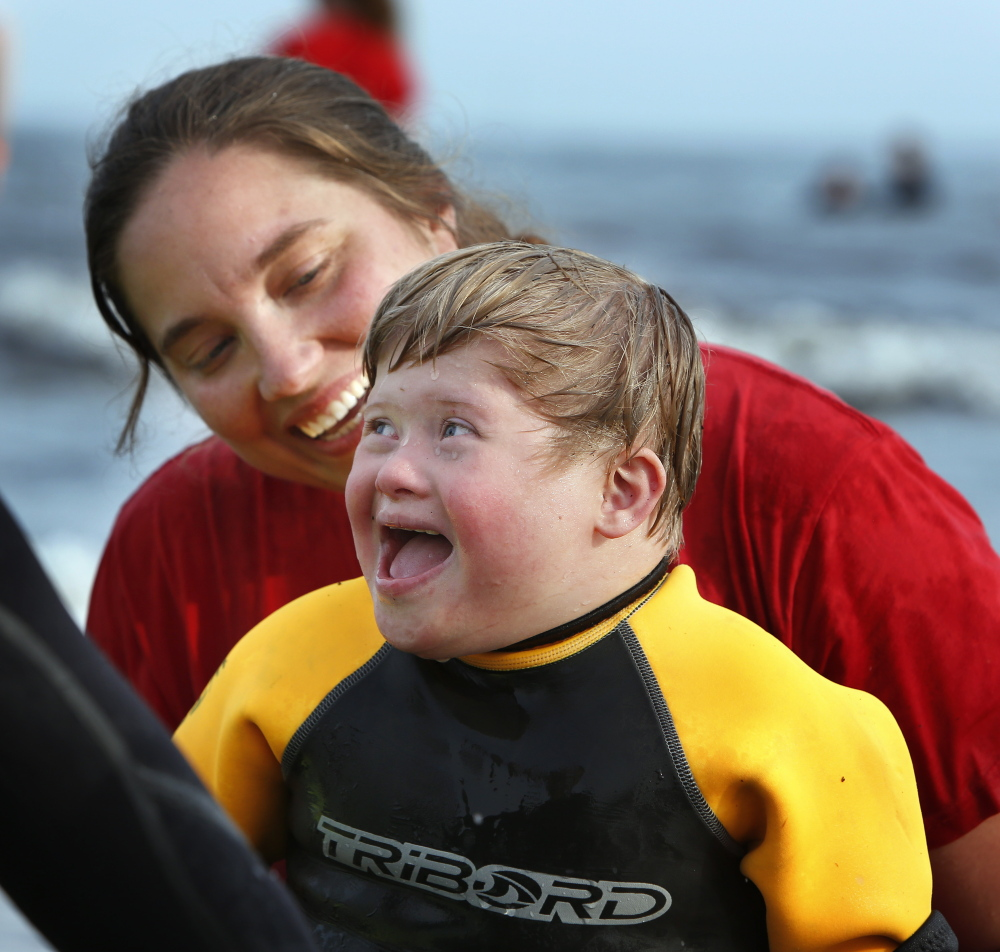 Michael Johnson, 6, of Cumberland is all smiles after riding a wave with the help of volunteer Casie Levesque of Old Orchard Beach. Gregory Rec/Staff Photographer