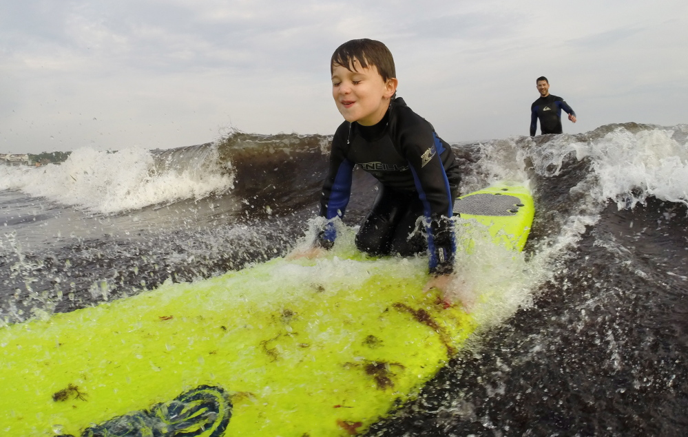 Maxwell House, 5, of Biddeford, rides a wave atop a surfboard. Gregory Rec/Staff Photographer