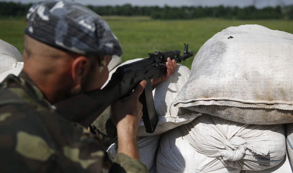 A pro-Russian separatist fighter looks out Friday from a checkpoint post near Donetsk, Ukraine.