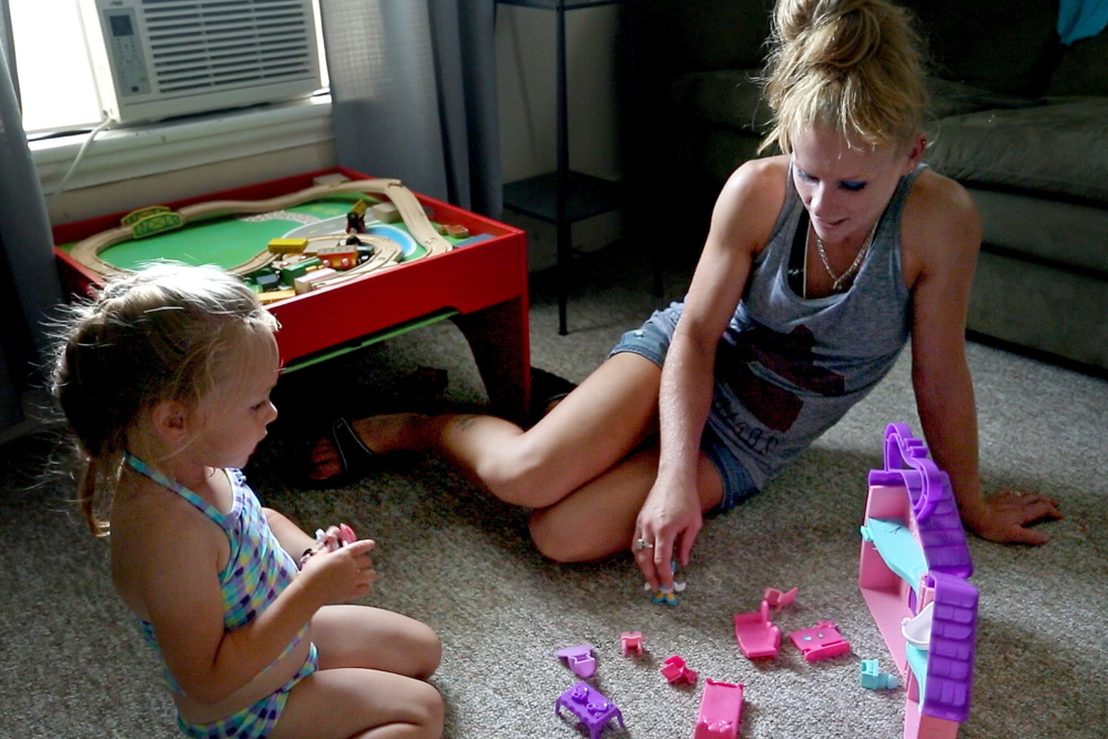 Alyssa Gray plays with her mother, Dawn Moores, in their Bucksport apartment. Alyssa is the daughter of Adam Gray.