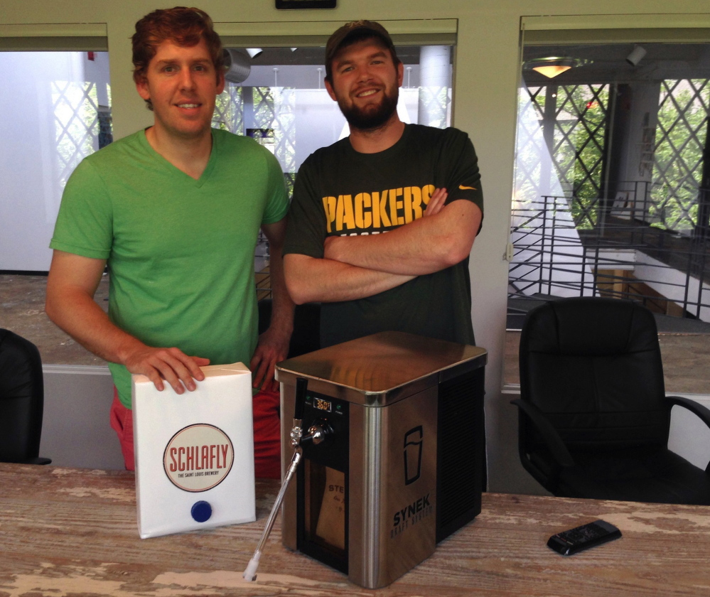 Synek's co-founder Steve Young, left, and strategic director Michael Werner with their beer dispenser, which is the subject of a successful Kickstarter campaign that has seen them raise more than $450,000 for development, manufacturing and marketing expenses.