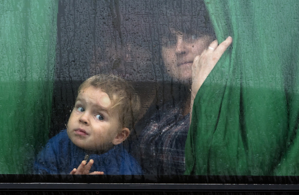 People in the city of Donetsk, eastern Ukraine, look out a bus window as they depart for Russia on Monday. Five busloads of internally displaced people from four towns left Monday morning for the Rostov region in Russia to ask for refugee status there.  The Associated Press