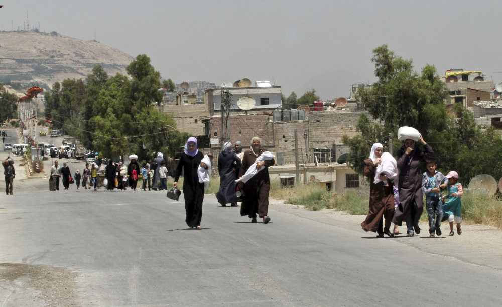 Syrians carry foodstuffs as they return to the rebel-held suburb of Moadamiyeh, near Damascus, following the entry of 13 Syrian Red Crescent trucks Monday.