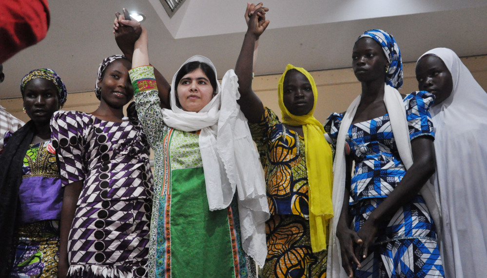Malala Yousafzai, center, raises her hands with some of the escaped kidnapped girls at a news conference in Abuja, Nigeria, on Monday.