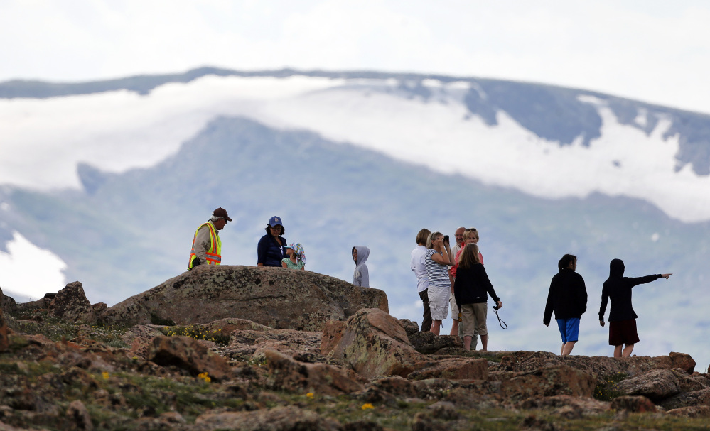 Volunteer Tundra Guardian Rick Beesley, far left, talks with visitors at a scenic overlook off Trail Ridge Road at Rocky Mountain National Park, west of Estes Park, Colo., on Monday. Lightning killed two people in the park over the weekend.