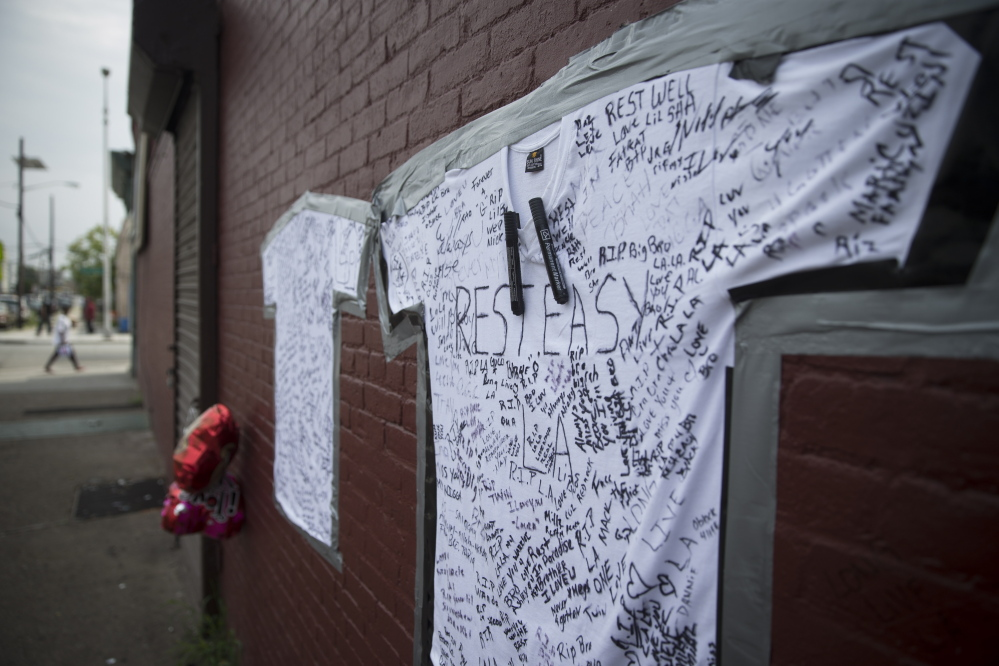T-shirts covered with written messages are taped on a wall at memorial to Lawrence Campbell, who allegedly shot and killed 23-year-old Jersey City police officer Melvin Santiago, Monday, July 14, 2014, in Jersey City, N.J. Campbell was also killed at the scene after police officers returned fire. (AP Photo/John Minchillo)