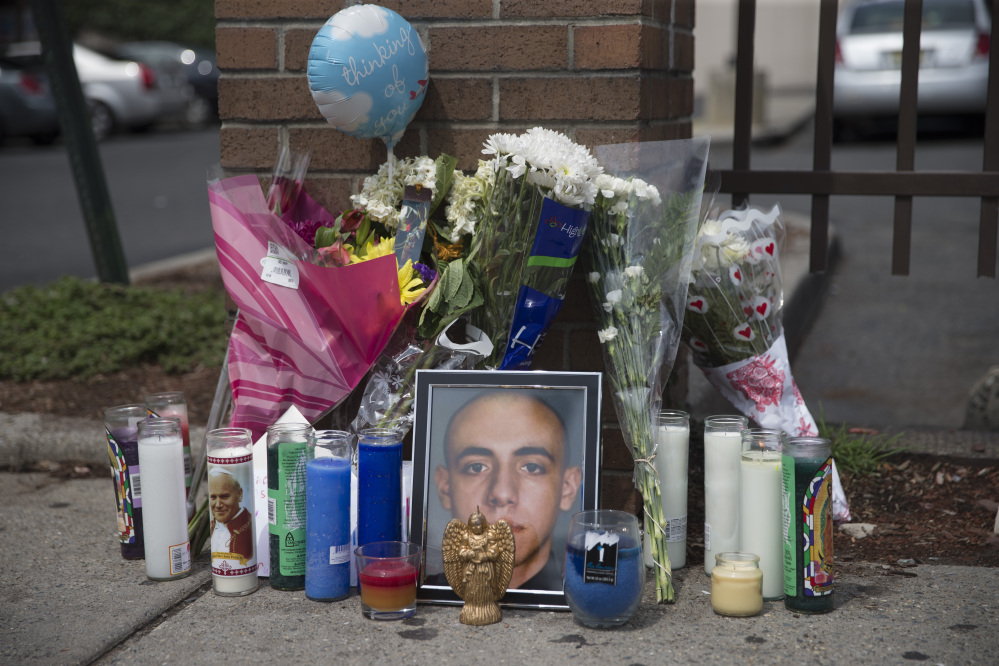 A memorial for 23-year-old Jersey City police officer Melvin Santiago stands at the Walgreens where he was fatally shot the previous day, Monday, July 14, 2014, in Jersey City, N.J. Santiago, who joined the force last July and was sworn in December, was fatally shot in the head inside his marked police car as he pulled up to the store. (AP Photo/John Minchillo)