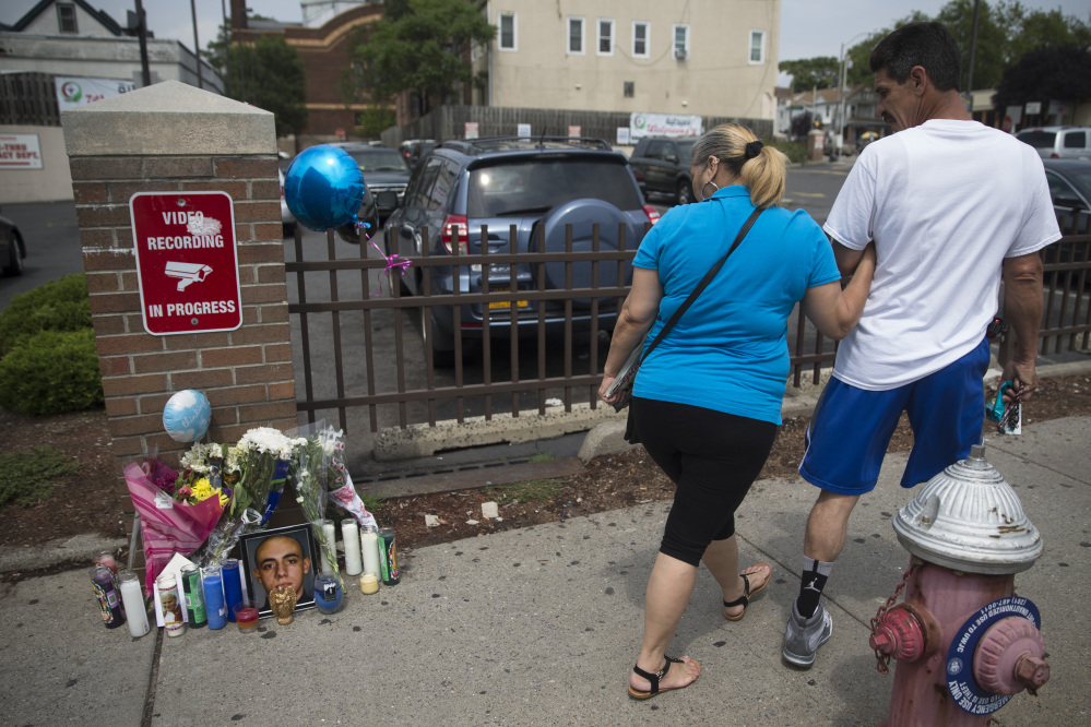 Pedestrians walk past a memorial for 23-year-old Jersey City police officer Melvin Santiago outside the Walgreens where he was fatally shot the previous day, Monday, July 14, 2014, in Jersey City, N.J. Santiago, who joined the force last July and was sworn in December, was fatally shot in the head inside his marked police car as he pulled up to the store. (AP Photo/John Minchillo)