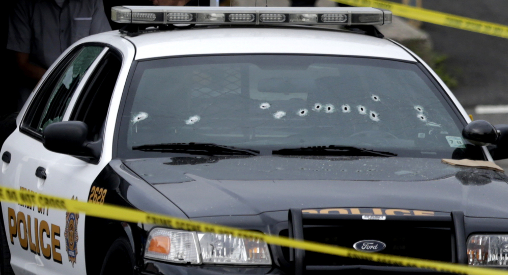 A Jersey City Police Department cruiser is seen with bullet holes on the windshield at the scene where an officer was shot and killed while responding to a call at a 24-hour pharmacy, Sunday, July 13, 2014, in Jersey City, N.J.  Officer Melvin Santiago was shot in the head while still in his police vehicle as he and his partner responded to an armed robbery call  at about 4.a.m., Jersey City Mayor Steven Fulop said in a statement.  Fulop said officers responding to the robbery call shot and killed the man who shot Santiago. He was not immediately identified. (AP Photo/Julio Cortez)