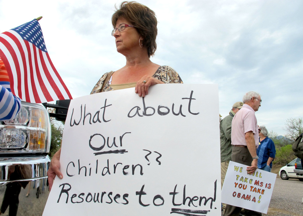 Deborah Pfaff joins other protesters near the entrance to a juvenile facility in Oracle, Ariz., where federal officials delayed a bus of Central American children from arriving. Pfaff was one of dozens of protesters on both sides of the immigration debate who showed up in the town near Tucson on Tuesday following reports that 40 children would arrive.