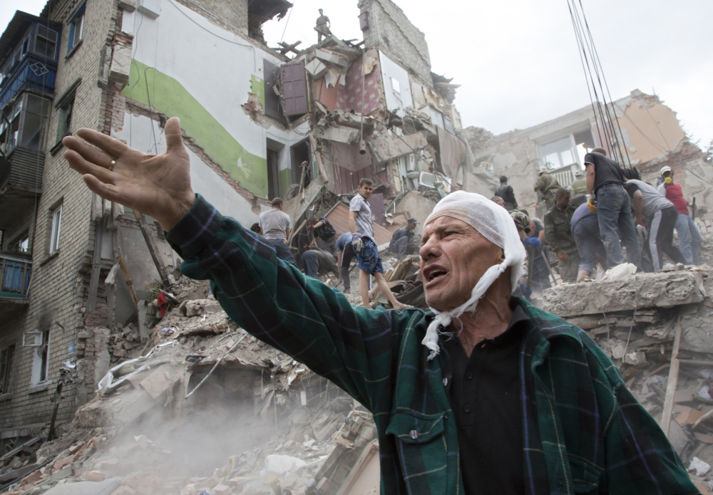 Igor Chernetsov, whose wife was killed in a building demolished by an airstrike, gestures near the collapsed structure in Snizhne, east of Donetsk, eastern Ukraine.