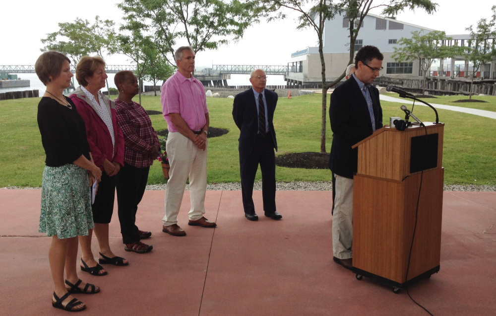 Wolfe Tone, right, Maine director of The Trust for Public Land, speaks along Portland's downtown waterfront Wednesday during an event announcing an initiative to develop a long-term plan for public parks and open space in the city.