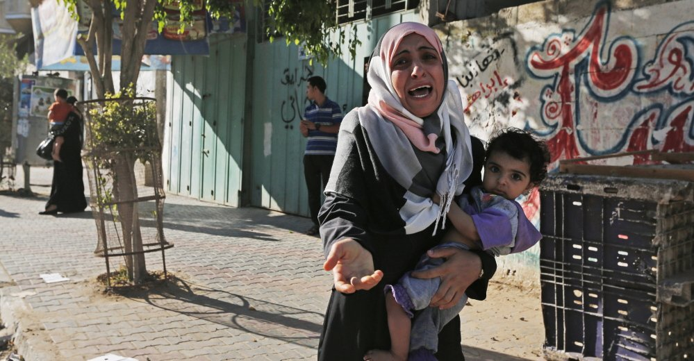 A woman cries as Palestinians flee their homes Wednesday in the Shajaiyeh neighborhood of Gaza City, after Israel airdropped leaflets warning people to leave the area.