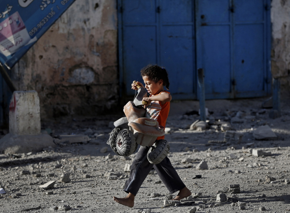 A Palestinian girl walks with a toy that she salvaged from debris of the el-Yazje apartment building which was destroyed following an overnight Israeli missile strike in Gaza City, Thursday.