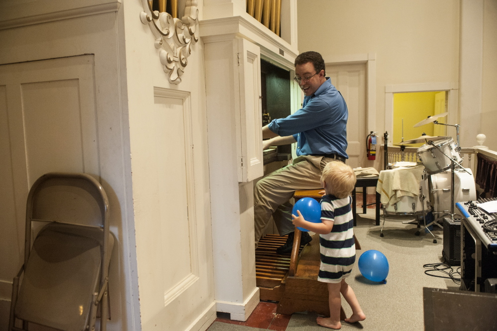 A young helper watches Aaron Robinson play the organ at the Damariscotta Baptist Church.