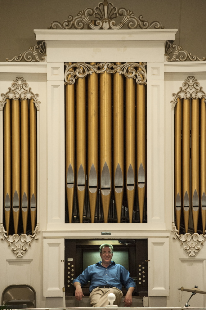 Aaron Robinson with the Damariscotta Baptist Church organ, which he was helping to restore.