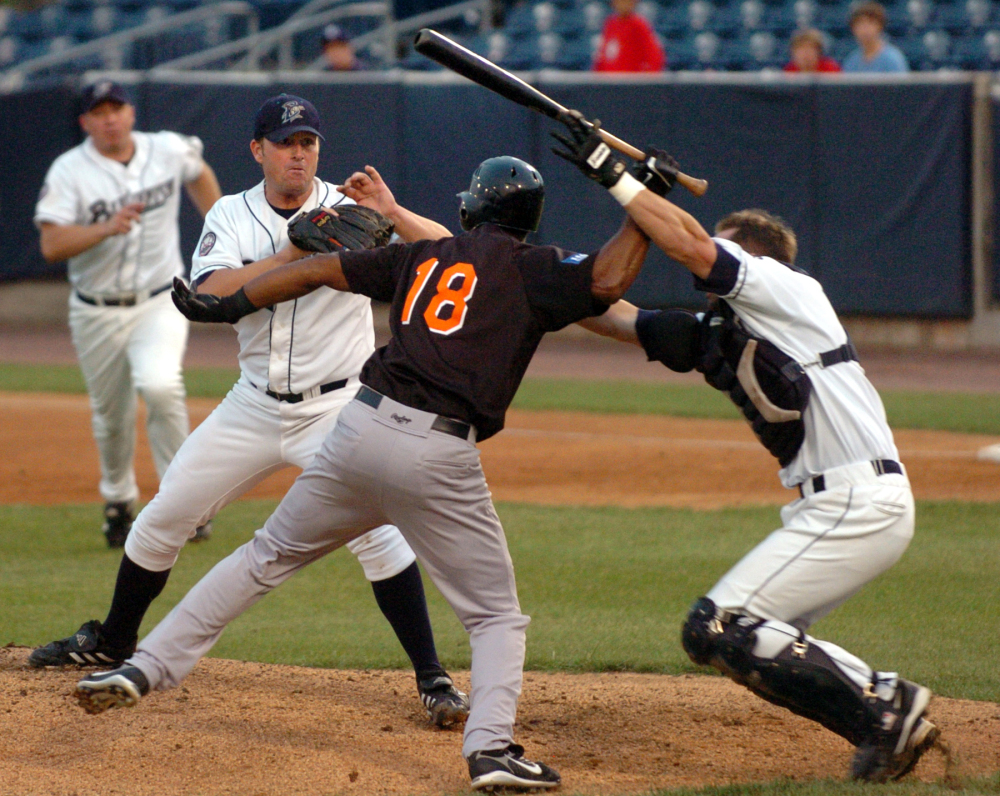 Bridgeport Bluefish catcher John Nathans, right, tries to prevent Long Island Duck's Jose Offerman (18) from hitting Bluefish pitcher Matt Beech with a bat during a fight in the first inning of an Atlantic League minor league baseball game in Bridgeport, Conn., in August 2007.